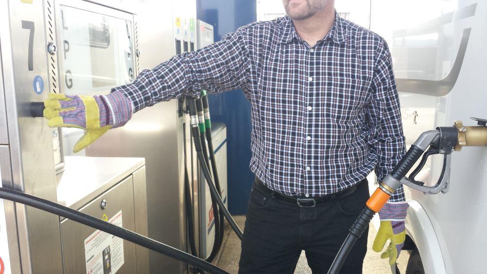 Tapfsäule Nr. 7 mit Schrift LPG, Mann mit Arbeitshandschuhen drückt auf den Knopf unter der 7, rechts Gaszapfpistole am Fahrzeug