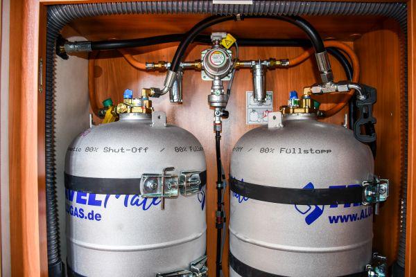 Frontansicht von zwei Gastankflaschen von Alugas fest eingebaut mit Stahlbändern, Betankungsschlauch verbindet beide Gastankflaschen und führt links zur Außenwand, Gasregler Duocontrol, zwei Gasfilter