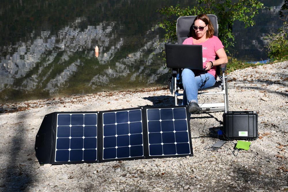 Links vorne ein ausgefalstetes Solarmodul in der Sonne stehend, rechts daneben ein schwarzer Plastikkoffer, davor ein Smartphone in grauer Hülle und ein E-Book in grüner Hülle. dahinter sitzt eine Frau mit Sonnenbrille, schulterlangen brauenn Haaren, rosa T-Schirt und blauer Hose in einem Hochlehner-Campingstuhl. Sie hat das rechte Bein übergeschlagen und darauf einen Laptop, in den sieh sieht. Alle Geräte sind an dem schwarzen Koffer angeschlossen.