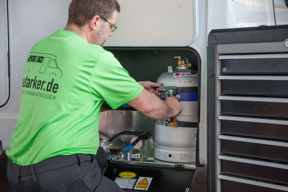 Andres Irmer kniet vor dem offenen Gaskasten eines Wohnmobils. Im Gaskasten steht eine Gastankflasche, Andreas hält rechts eine Ratsche und befestigt das Stahlband. Rechts ist ein Teil eines Werkzeugwagens im Bild.