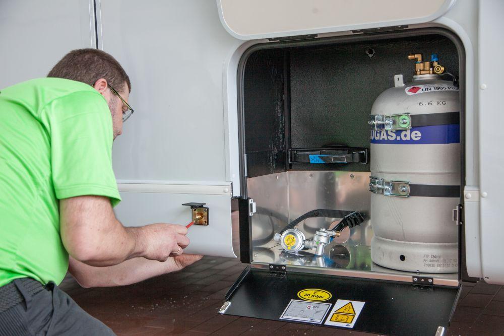 Andreas Irmer kniet neben dem offenen Gaskasten des Wohnmobils und schrauft den Anschluss für die Außenbetankung an. Im Gaskasten befinden sich eine befestigte Gastankflasche und ein Gasregler.