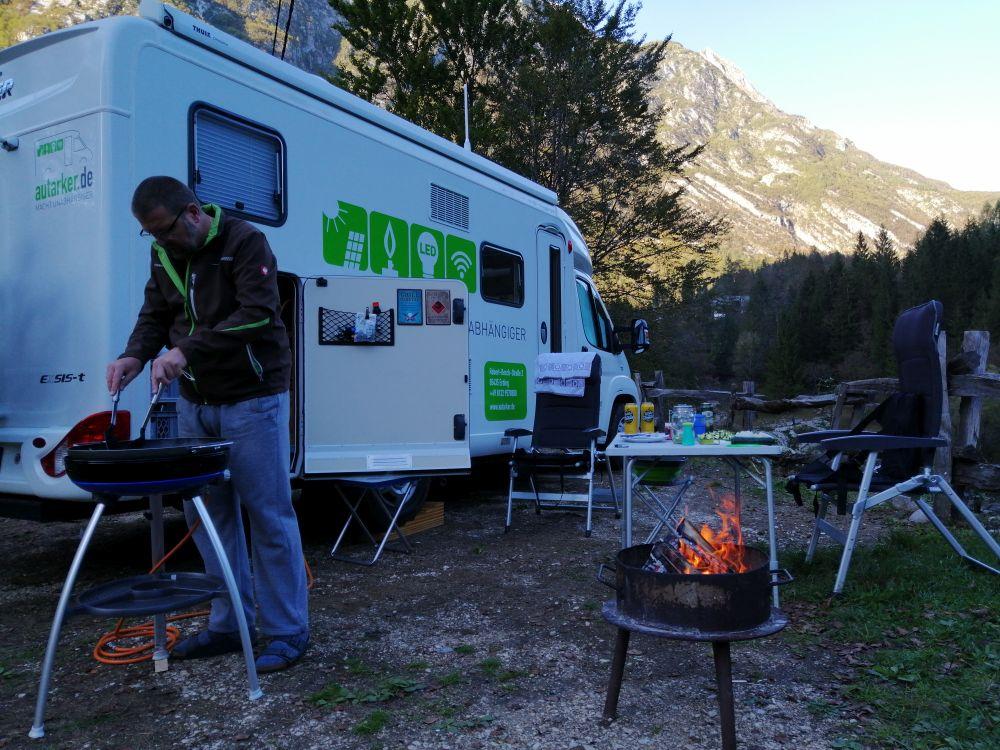 Wohnmobil mit offener Garagentür vor Baum, im Hintergrund Berg und blauer Himmel, im Vordergrund Mann der grillt, Gasgrill mit Gasschlauch, Feuerschale mit Feuer, im Hintergrund Tisch und Stühle