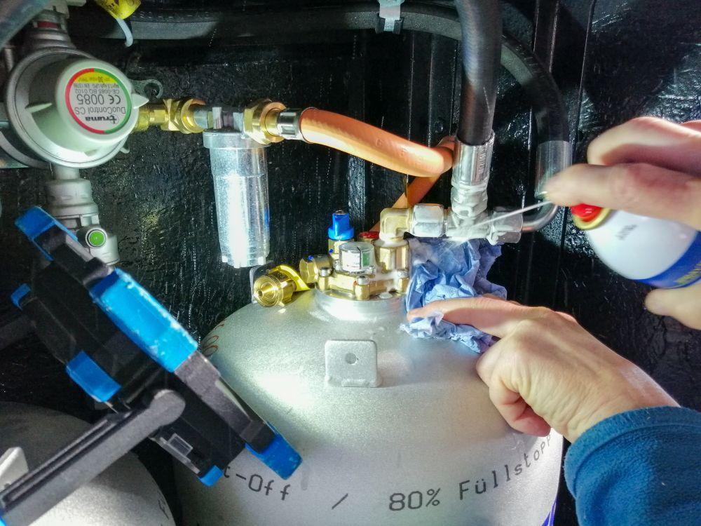 Im Gaskasten, Gasregler Truma DuoControl, Entnahmefilster, links eine Lampe, Rechts eine Hand mit Sprühflasche sprüht Flüssigkeit auf den Kopf der Gastankflasche, wo ein Schlauch angeschlossen ist, die linke Hand hält ein Tuch unter die Stelle, auf die die Flüssigkeit trifft.
