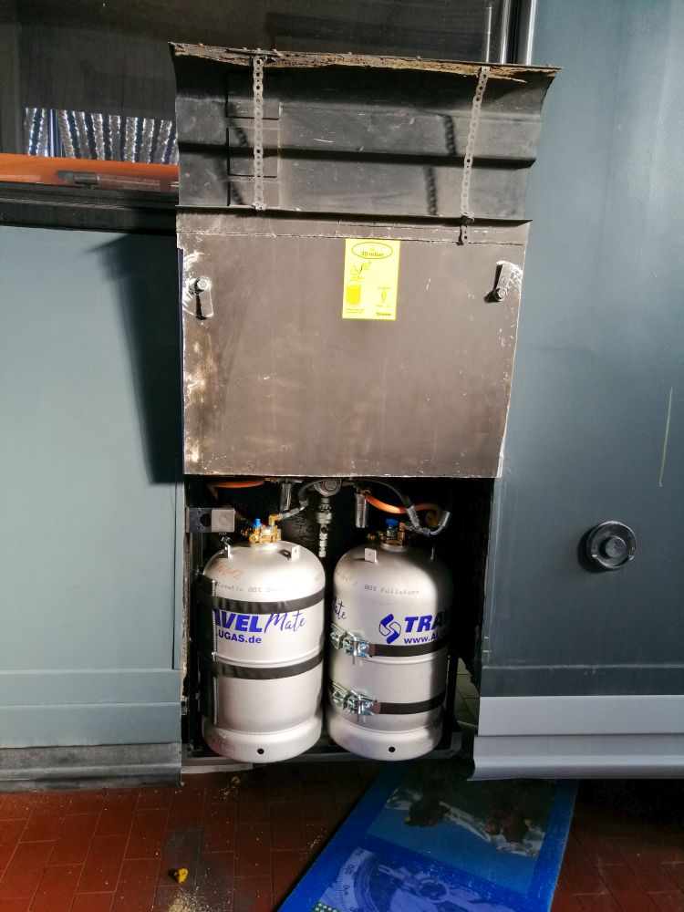 zwei Gastanklfaschen im noch unten offenen Gaskasten eines grauen Wohnmobils. Die Gasklappe ist nach oben offen. Isomatte liegt teilweise sichtbar auf dem Boden.