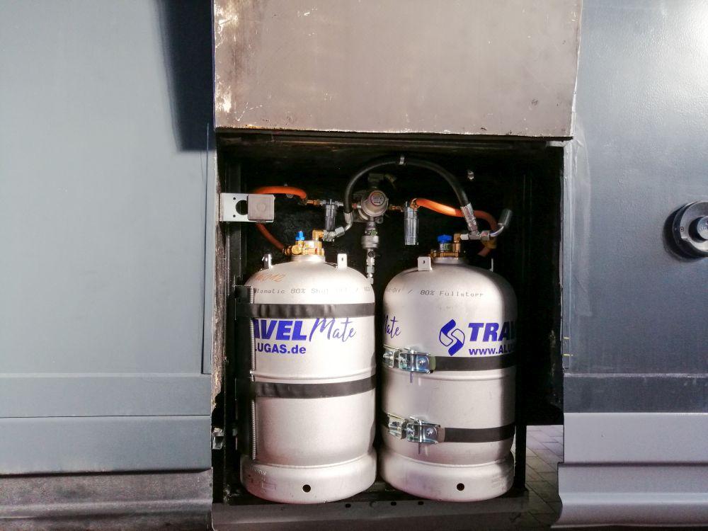 Zwei Alugas Tankflaschen in einem offenen Gaskasten von einem grauen Wohnmobil. Winkel mit Betankungsanschluss im Gaskasten, Gasregler DuoControl mit zwei Filtern und Schläuche.