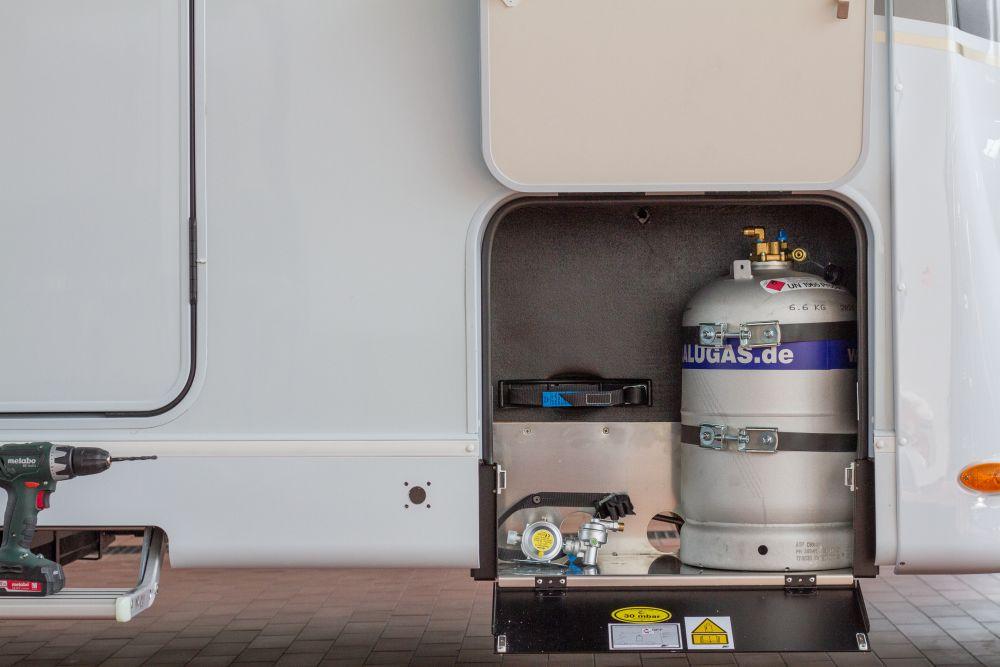 Einbausituation an einem Wohnmobil mit offenem Außengaskasten, Akkubohrer, Löchern in der Fahrzeugschürze für die Betankung einer eingebauten Alugas Tankflasche und im Gaskasten liegendem Gasregler.