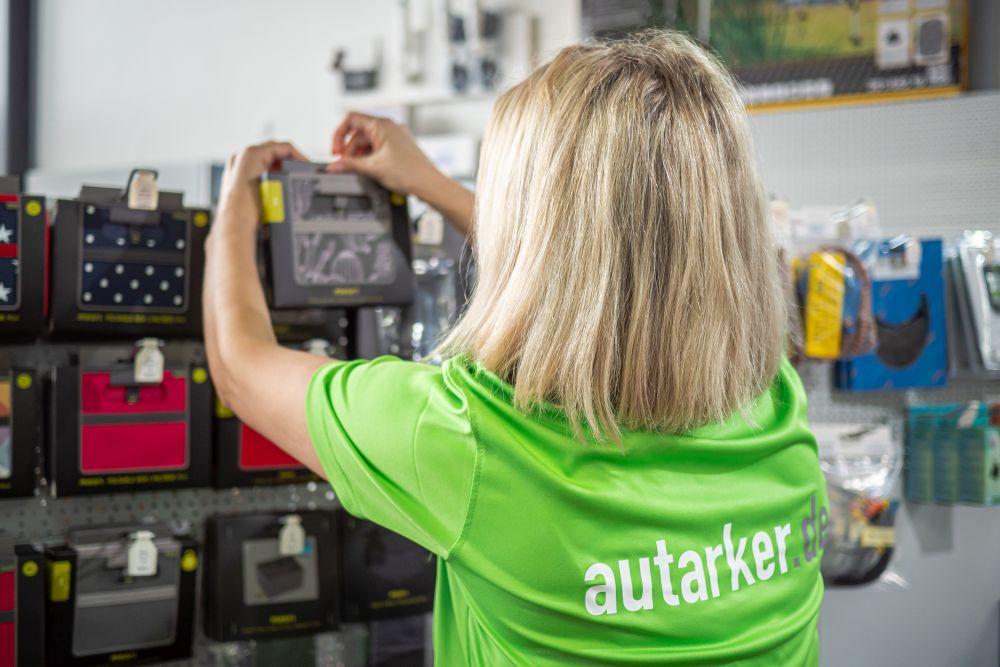 Frau mit blonden, schulterlangen Haaren und grünem T-Shirt mit weißer Schrift autarker und grauer Schrift .de steht vor einem Ladenregal, an dem bunte, zusammengefaltete (Meori-)Boxen hängen. Sie hängt eine Box auf.
