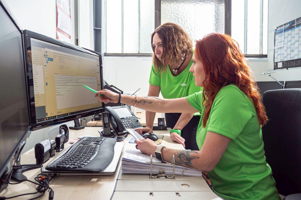 In einem Büro. Links zwei Bildschirme, davor eine Tastatur auf dem Schreibtisch, davor ein aufgeschlagener Ordner, im Hintergrund ein Telefon. Am Schreibtisch sitzend eine Frau im grünen T-Schirt mit roten langen Haaren, hält in der linken Hand eine Zettel und zeigt mit eine grünen Kuli in der rechten Hand auf den rechten Bildschirm. Frau mit braunen, schulterlangen Haaren, in gründem T-Shirt steht neben der anderen Frau und Stützt sich auf den Schreibtisch. Beide schauen in den rechten Bildschirm.