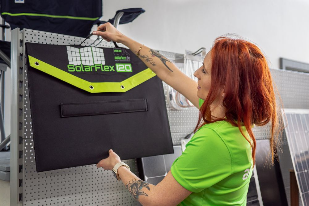 Frau in grünem T-Shirt, mit roten langen Haaren, hängt eine zusammengefaltete Solartasche mit der Beschriftung SolarFlex120 in ein Regal.